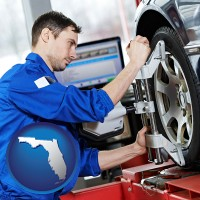 florida a mechanic adjusting a wheel alignment machine clamp