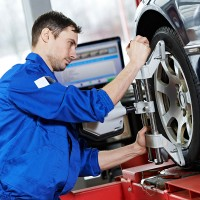 a mechanic adjusting a wheel alignment machine clamp